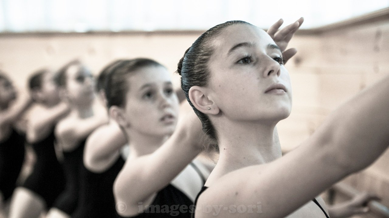 Photo by in house photographer, Sori Gottdenker, of her students practicing 2nd Arabesque at the Barre in the dance studio