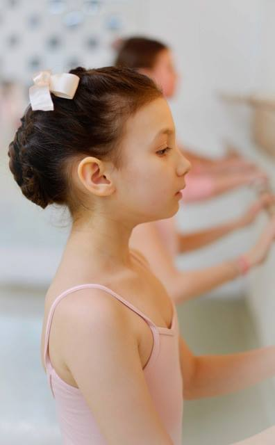 Photo by in house photographer Sori Gottdenker of an 8 year old student practicing proper posture while facing the barre in the dance studio